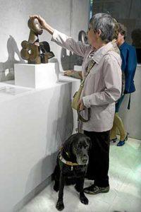 mujer ciega toca una escultura en un museo