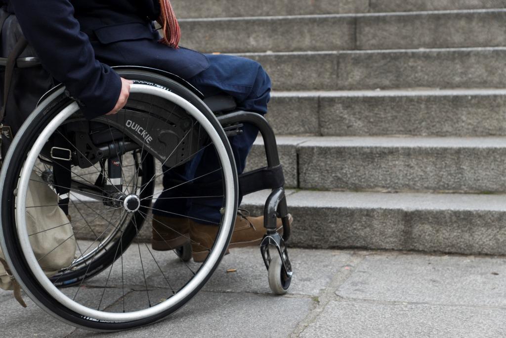 Imagen de una persona que se desplaza en silla de ruedas frente a un tramo de escaleras