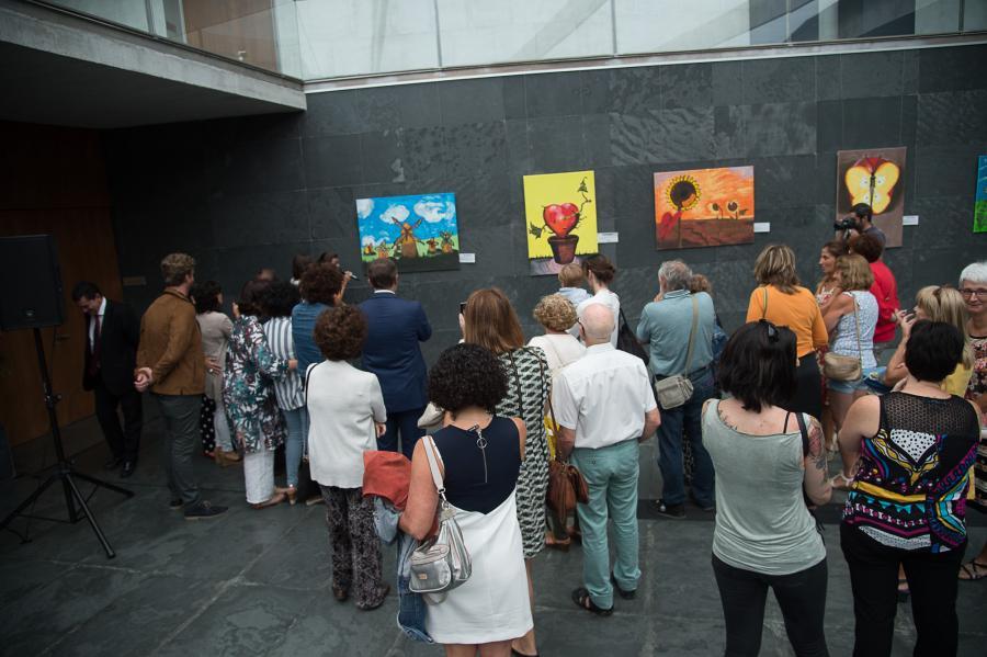 grupo de personas mirando cuadros que están colgados en la pared