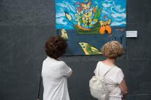 un cuadro en la pared y dos personas mirándolo