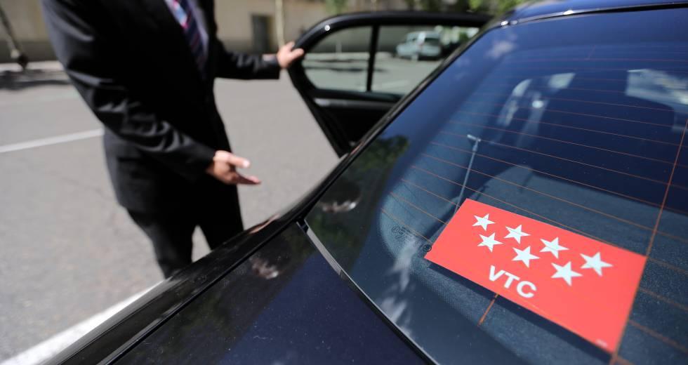 Un conductor de VTC abre la puerta de su vehículo. El Pais