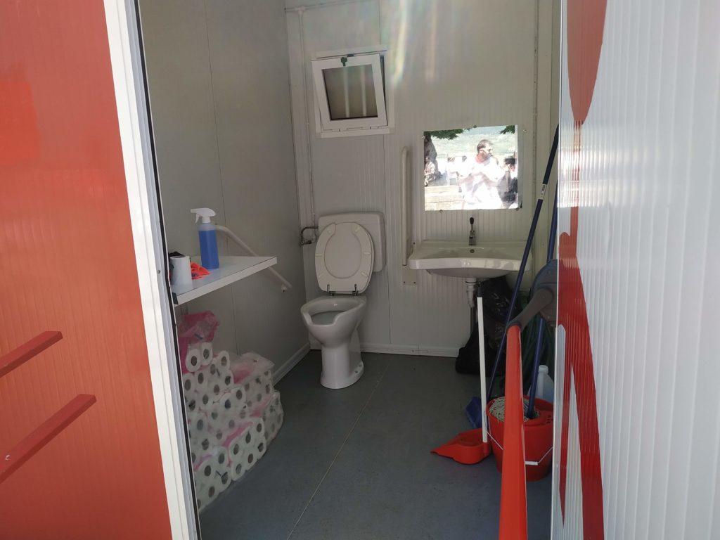 baño adaptado de sanfermines usado como almacen con rollos de papel higiénico, fregona, recogedor y material de limpieza