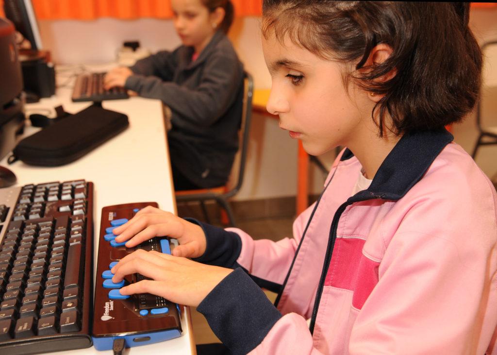Alumnas utilizando ordenadores adaptados, uno de ellos con linea braille.