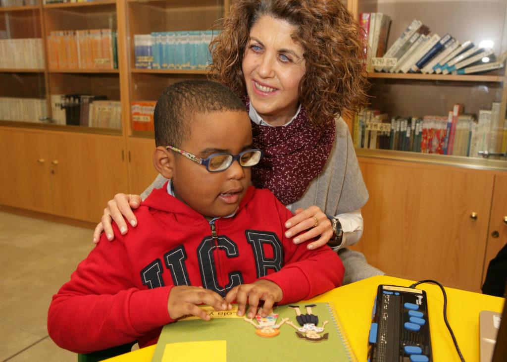 alumno y un profesor con el metodo braitico - lectura braille - figuras en relieve