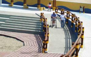 hombre con andador por una rampa al lado de una escalera