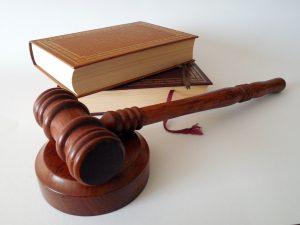 Imagen de un mazo junto a unos libros de derecho