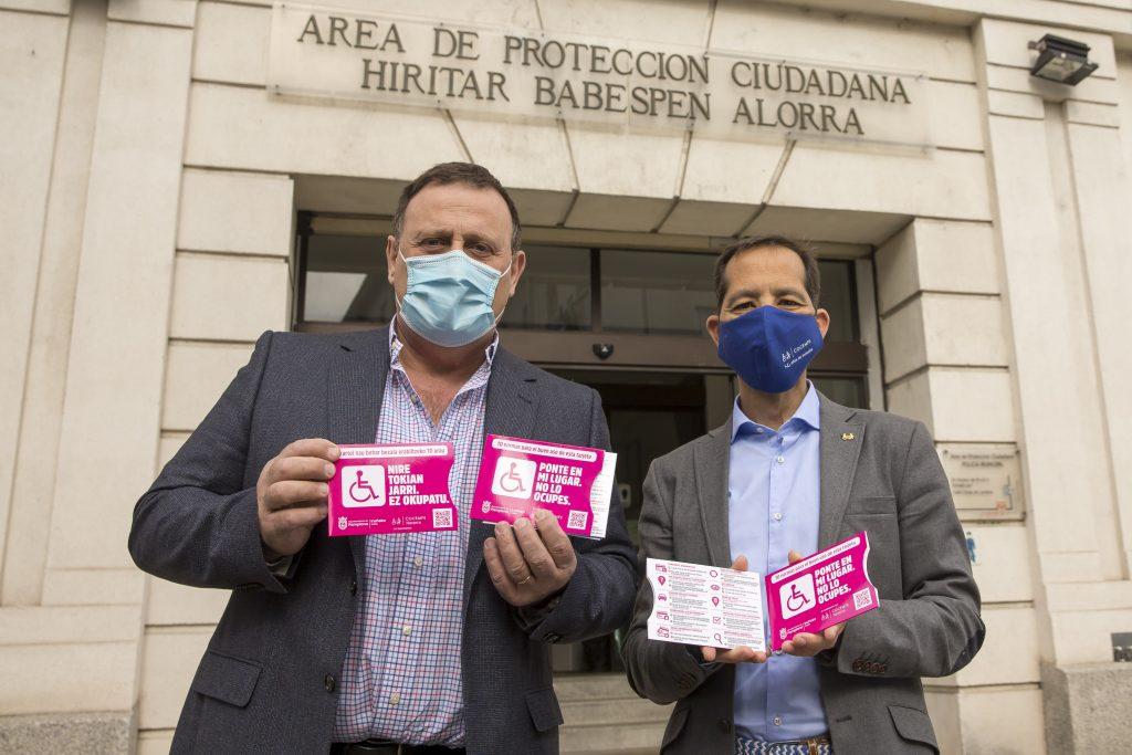 Javier Labairu y Manuel Arellano posan mostrando las fundas de las tarjetas de aparcamiento