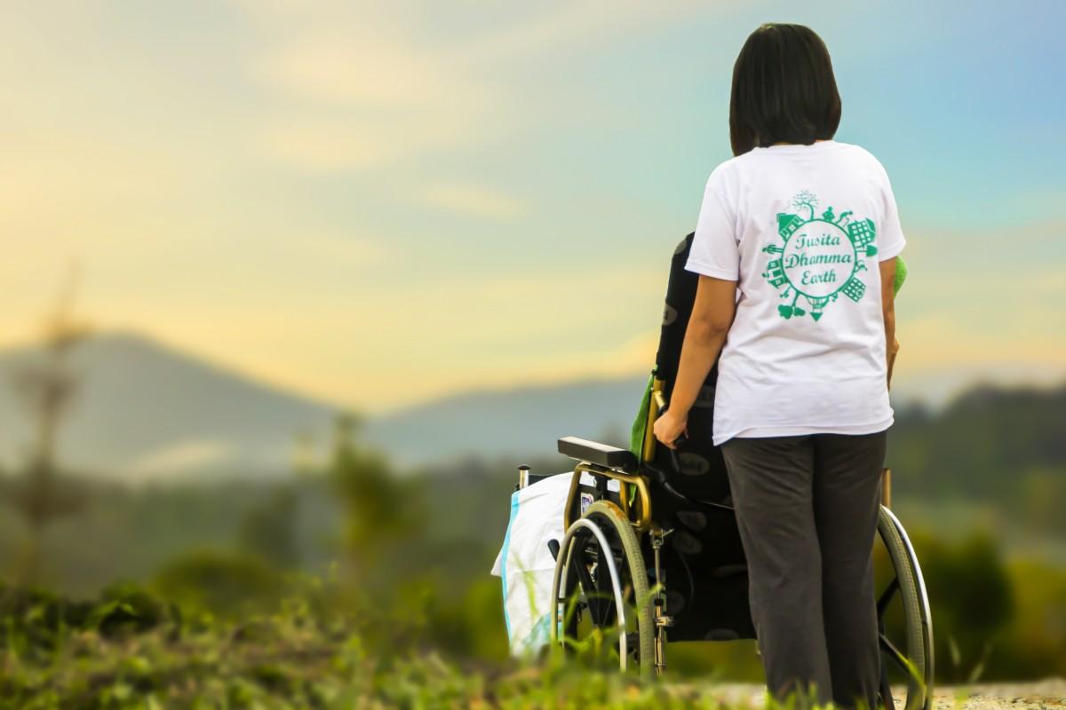 Imagen de una persona en silla de ruedas ayudada por otra