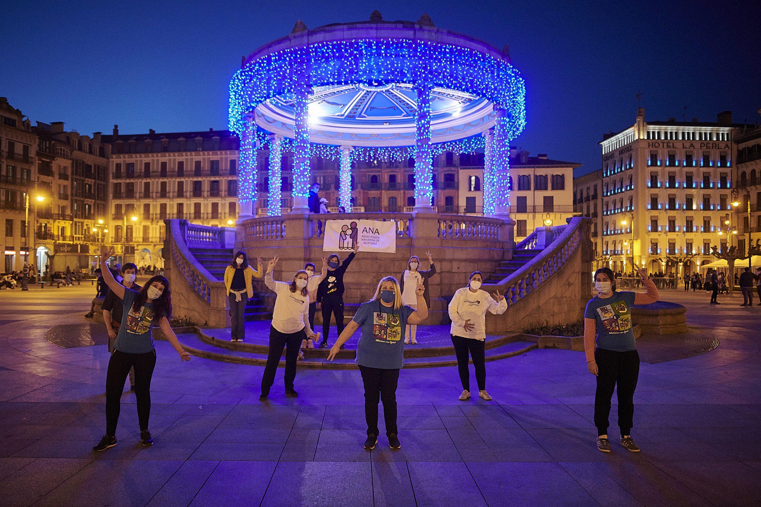 Integrantes de la Asociación ANA frente al kiosco de la Plaza del Castillo iluminado de azul