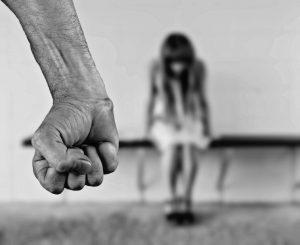 Imagen del puño de un hombre frente a la silueta difuminada de una mujer
