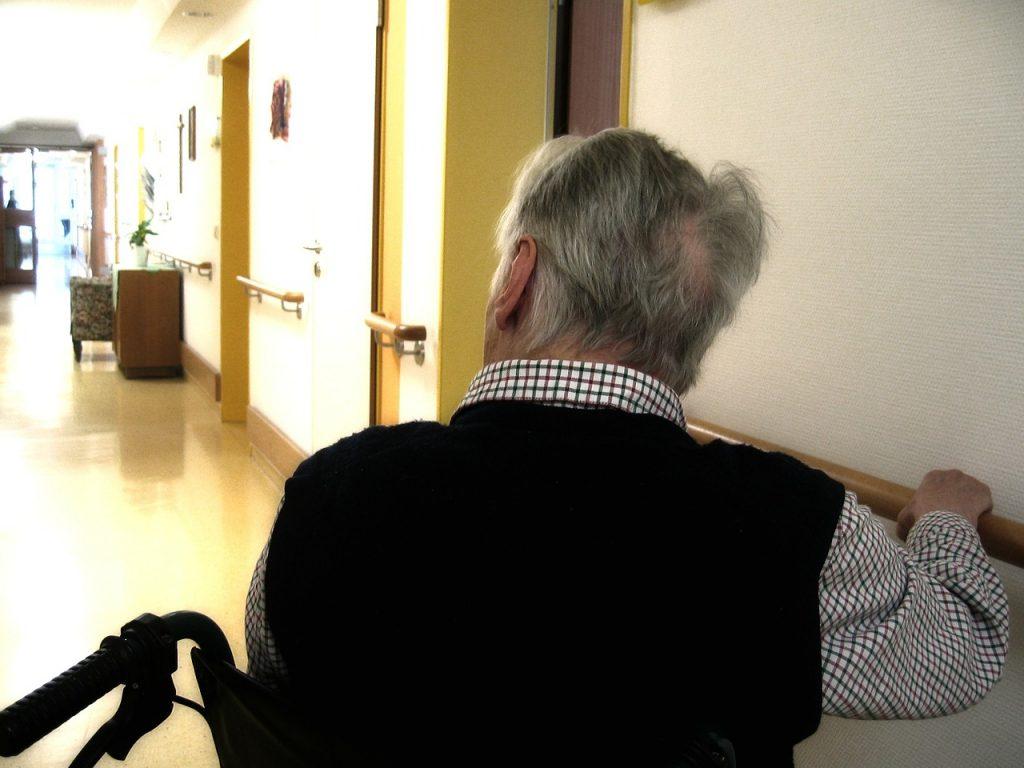 Hombre mayor en silla de ruedas en el pasillo de una residencia