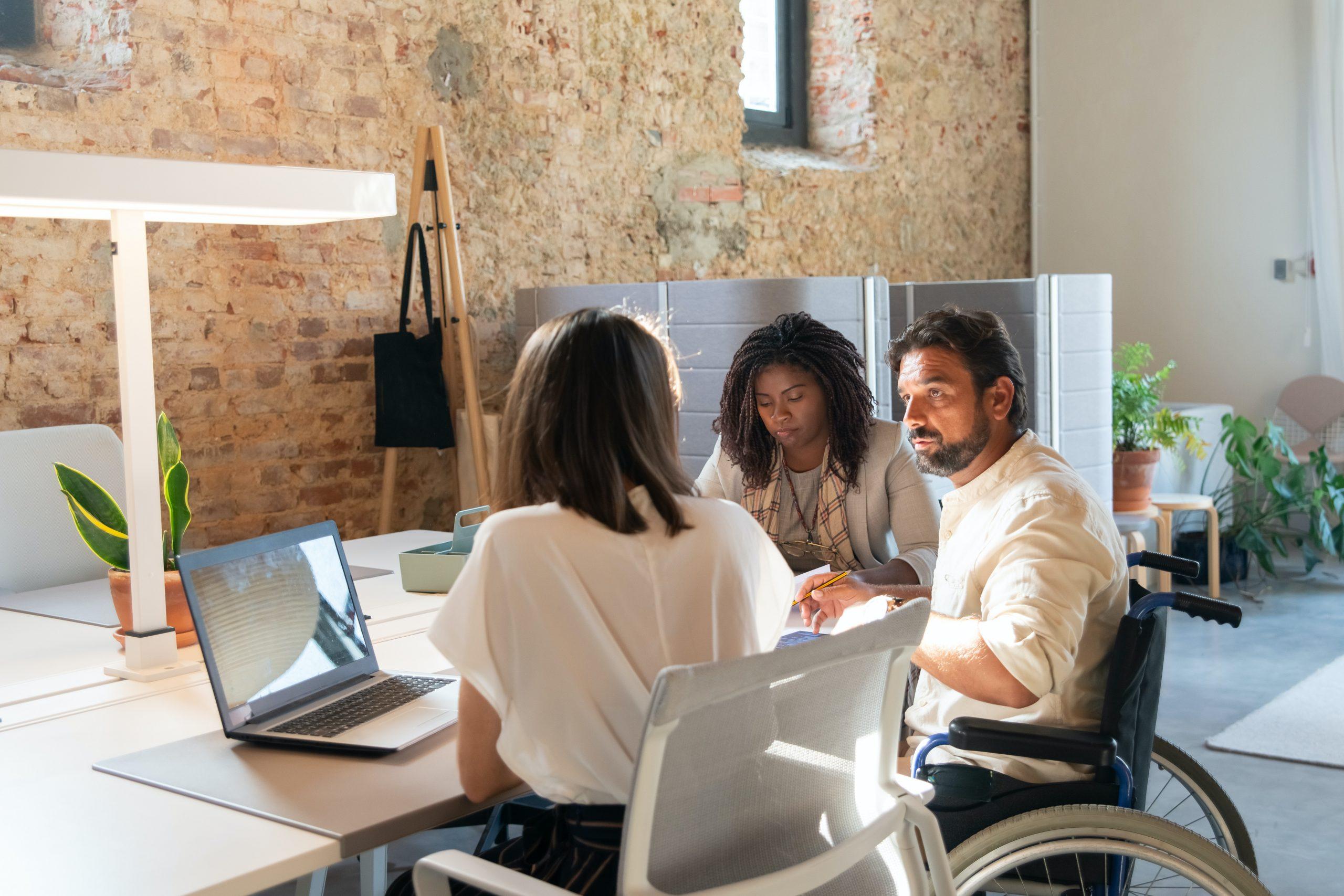 Imagen de tres personas entorno a una mesa de trabajo, una de le ellas en silla de ruedas