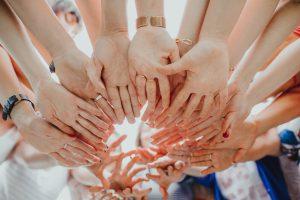 Imagen de varis manos que convergen en un mismo punto