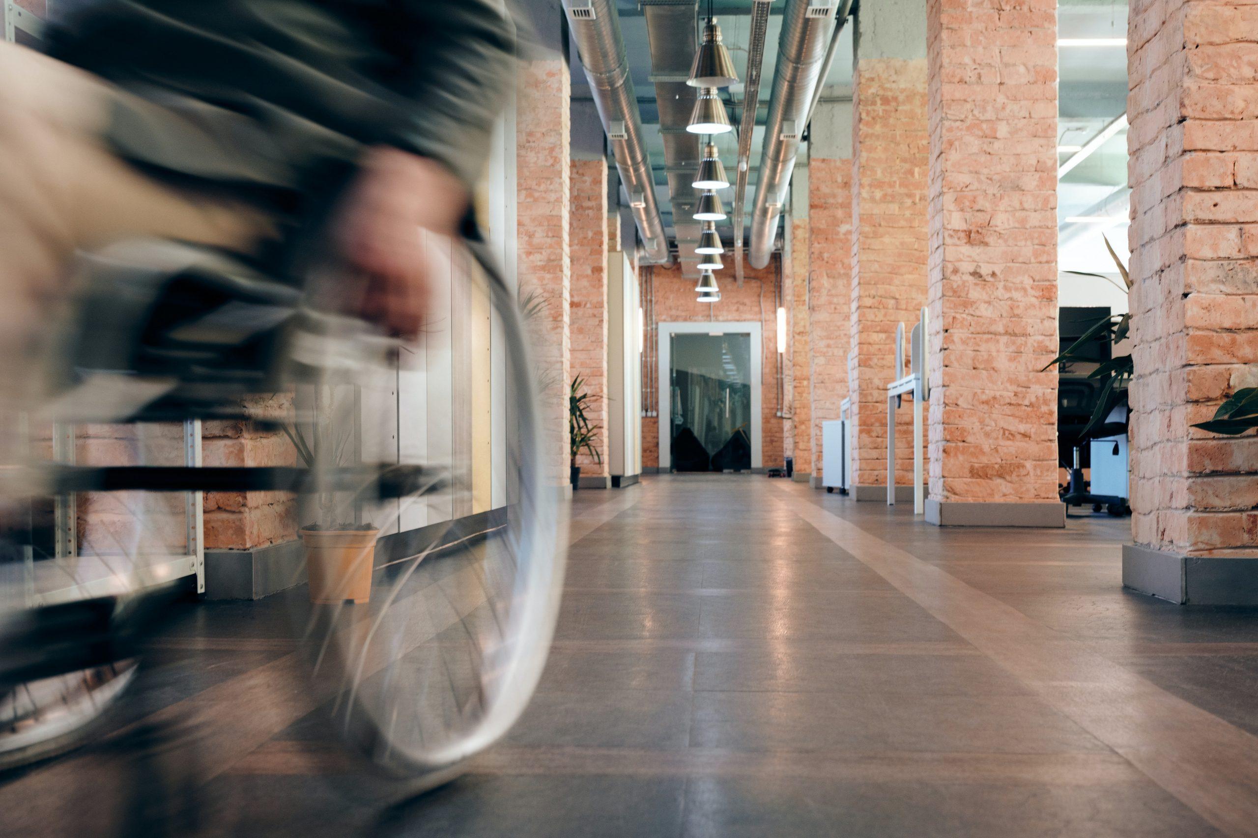 Persona usuaria de silla de ruedas atravesando un pasillo en el interior de un edificio