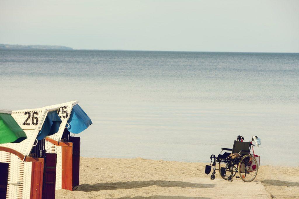 Imagen de una silla de ruedas sobre la arena de una playa