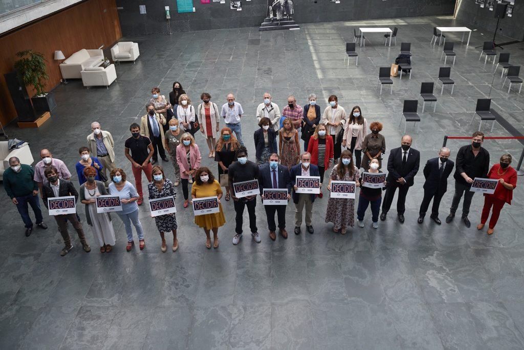 Foto de familia de los asistentes al acto en el Atrio del Parlamento de Navarra